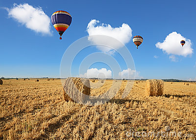 Three colorful balloons flying over the field