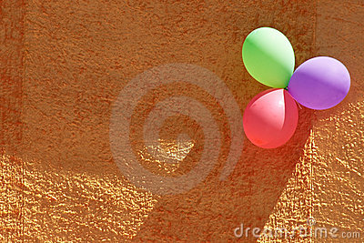 Three colorful party balloons and orange textured wall
