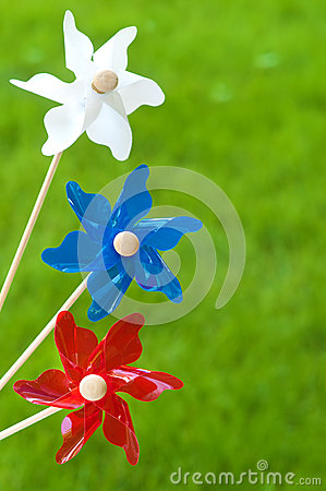 Three Colorful Pinwheels Against Grass Background