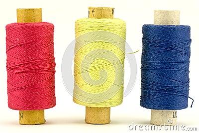 Three colorful thread spools