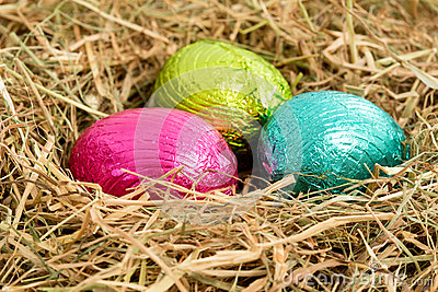 Three colouful easter eggs nestled in straw nest