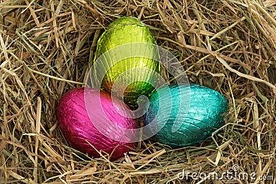 Three easter eggs nestled in straw