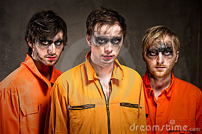 Three criminals in orange uniforms
