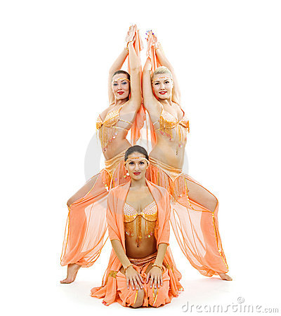 Three dancers in bright arabian stage costumes