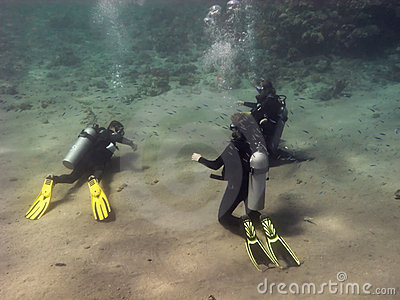 Three divers are training at the sea bottom