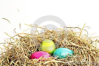 Three easter eggs nestled in straw nest