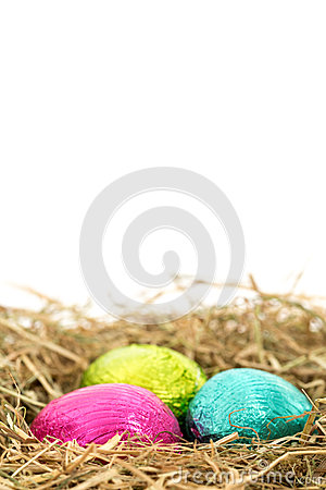 Three foil wrapped easter eggs nestled in straw nest