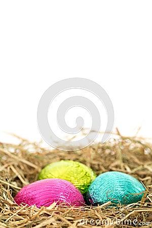 Three foil wrapped easter eggs nestled in straw nest
