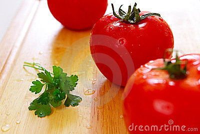 Three fresh tomatoes with water drops on them