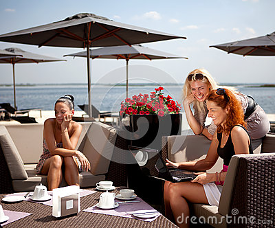 Three friends in a cafe on the beach