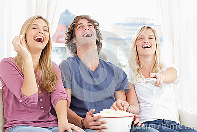 Three friends eating popcorn while laughing