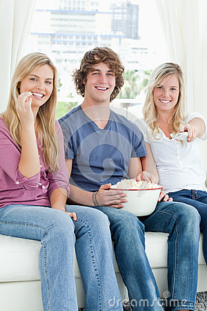 Three friends eating popcorn while smiling
