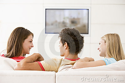 Three friends in living room watching television