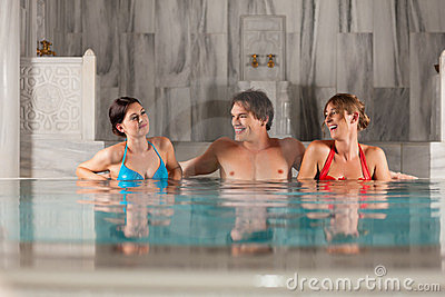 Three friends in swimming pool or thermal bath