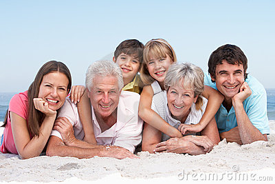 Three Generation Family Relaxing On Beach