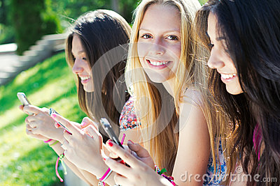 Three girls chatting with their smartphones