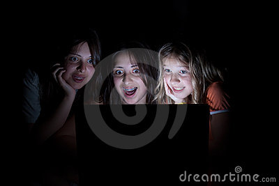 Three girls on the computer at night