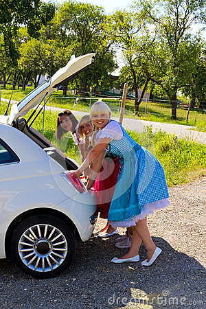 Three girls in Dirndl and her car
