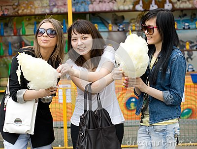 Three girls eating candy floss