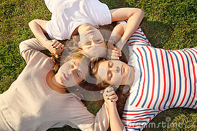 Three girls hold hands and lie on grass.