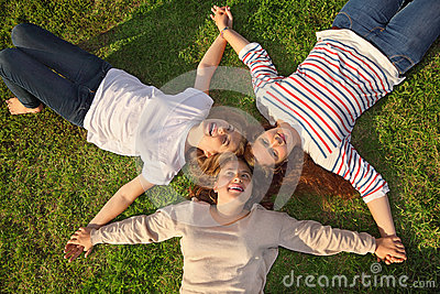 Three girls hold hands and lie on grass