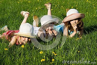 Three girls lie in the grass