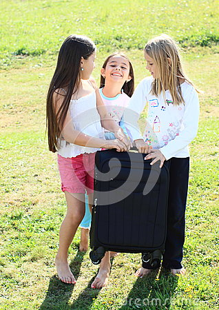 Three girls prepared for traveling with suitcase