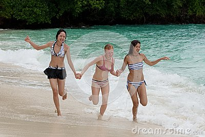 Three girls run on the beach