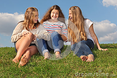 Three girls sit at grass, chat and laugh