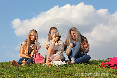 Three girls sit on grass with mobile phones