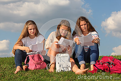 Three girls sit on grass and read something