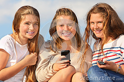 Three girls sit with mobile phones and smile