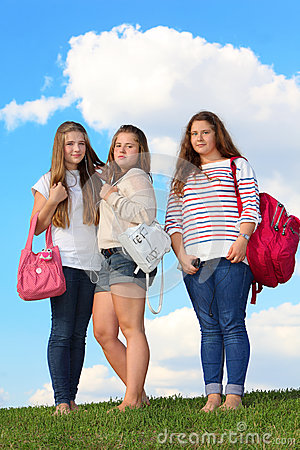 Three girls stand with bags on grass