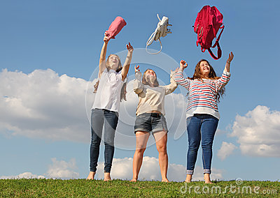 Three girls throw up bags and stand at grass