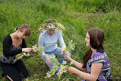 Three girls is twist flowers into a wreath