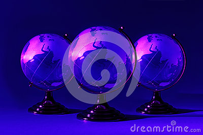 Three glass globes at stand is illuminated by pink