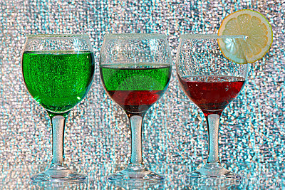 Three glasses of green and red liquor and lemon