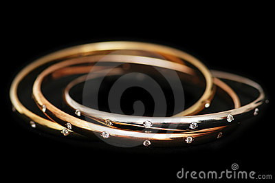 Three gold bracelets isolated