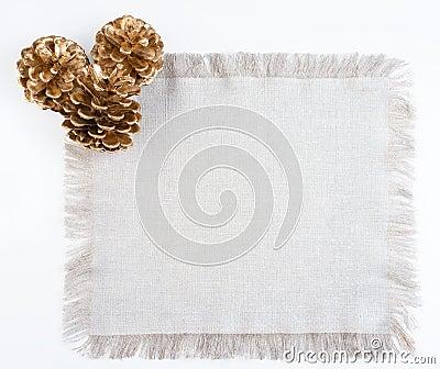 Three golden pines cones on linen tissue