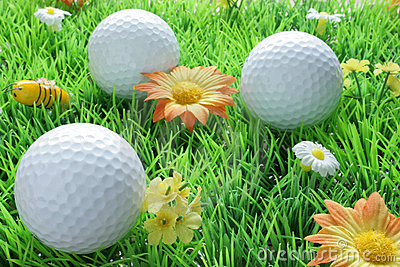 Three golf balls on artificial grass