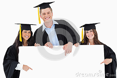 Three graduates pointing to the blank sign