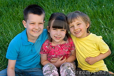 Three happy children in grass