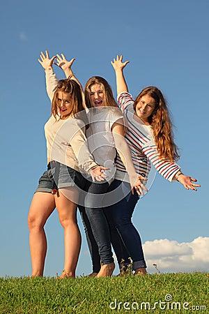 Three happy girls pose at green grass