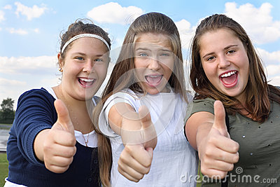 Three happy girls scream and thumb up outdoors