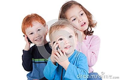 Three happy kids talking on mobile phones