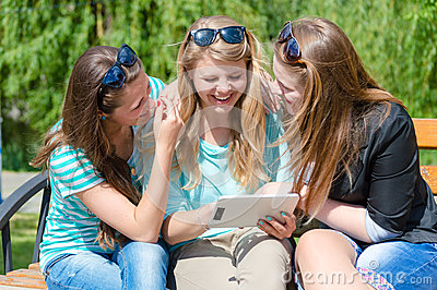 Three happy smilng young women friends and tablet computer