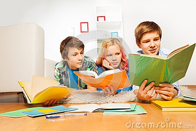 Three young teen kids reading books laying on the floor of living room