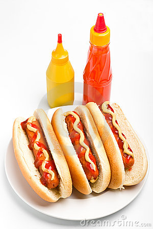 Three hotdogs with mustard and ketchup bottles
