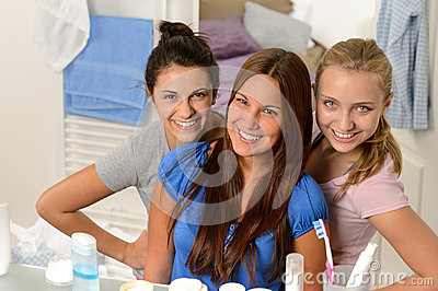 Three young girl friends posing in bathroom