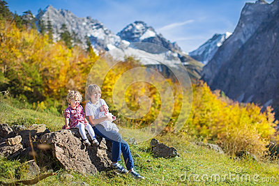 Three kids in beautiful snow covered mountains